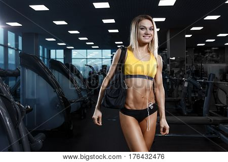 Sexy  Sport Girl With Headphones Relaxing In The Gym