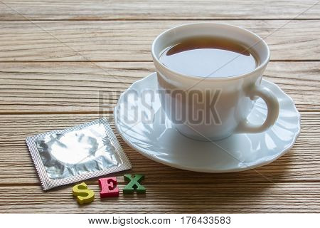 word sex condom and a cup of coffee. coffee beans on old wooden table