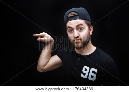 handsome man with beard pointing copy space. young man in t-shirt looking at camera and pointing away against black background