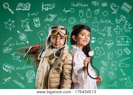 Kids and education concept - Small indian boy and girl posing in front of Green chalk board with doodles in pilot fancy dress and doctor costume with stethoscope, wanna be pilot or doctor