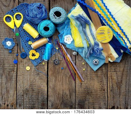 Yellow And Blue Accessories For Needlework On Brown Wooden Background. Knitting, Embroidery, Sewing.