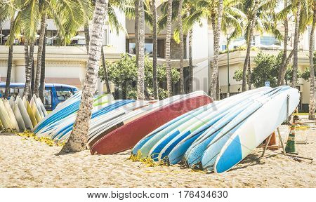 Multicolored surfboards at Waikiki Beach in Honolulu Hawaii - Surf boards at tropical exclusive destination in south east Asia - World famous surfing location spot on vivid retro vintage filtered look