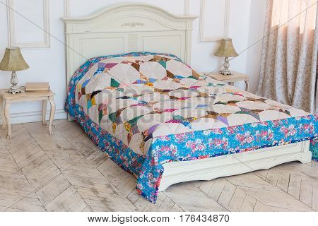 large double bed with a colored patchwork quilt in the white interior. scrappy blanket on the bed closeup.
