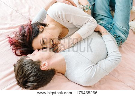 In the bedroom a loving couple in jeans on a big pink bed