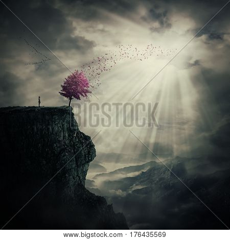 Young man standing on the peak of a cliff watching at a strange purple tree that cast its leaves in the wind over valley. The tree of life symbol journey and discover.