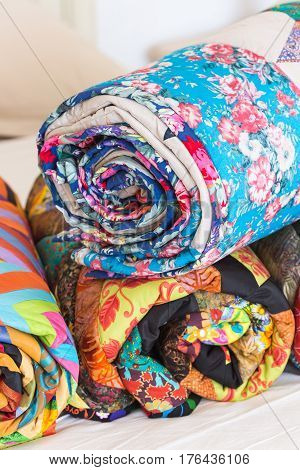 Three colored patchwork quilts twisted into close up. Colorful scrappy blankets folded as background. Handmade.