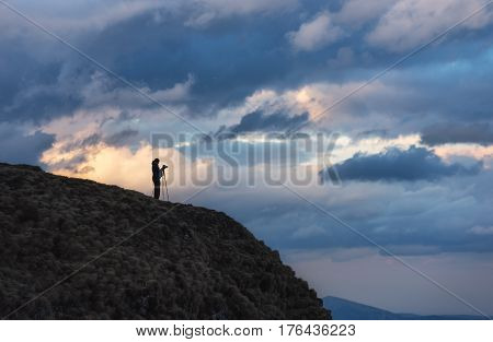 Photographer on a mountain cliff taking picture of a sunset with camera and tripod in cold weather