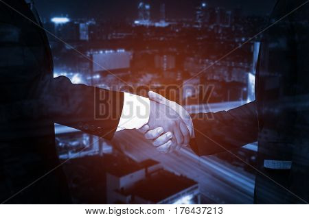 Double exposure of businessman handshake, business concept, successful business meeting on night city background, color tone effect.