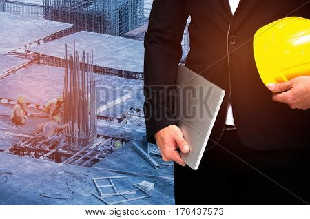 double exposure of businessman hold in hand yellow safety helmet and laptop computer notebook industrial concept on construction site workers background, color tone effect.