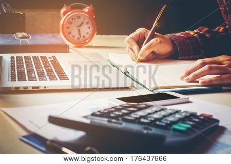 Businessman's Hands With Calculator At The Office Financial Data Analyzing Hand Writing And Counting