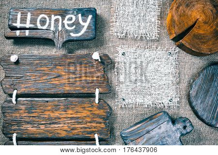 Dark wood boards, wood slice and burlap pieces as frames on burlap background. Wooden signboard with text 'Honey' as title bar. Rustic style template for food and drink industry