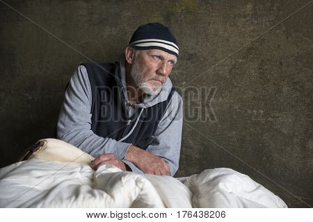 Mature homeless man sitting in an old blanket outdoors