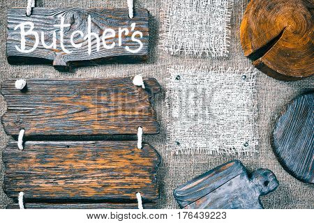 Dark wood boards, wood slice and burlap pieces as frames on burlap background. Wooden signboard with text 'Butchers' as title bar. Rustic style template for food and drink industry