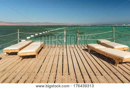 Pier with chaise longues in the sea in resort. Summer vacation