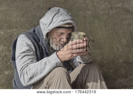 Mature homeless man begging outdoors with a tin can