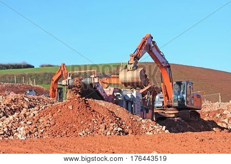 Stone crusher and digger on a construction site