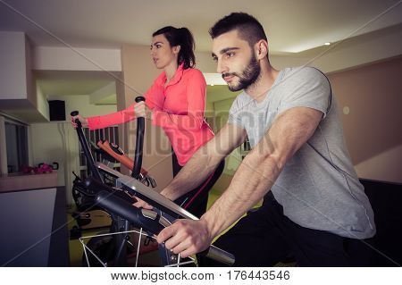Sporty Woman Using Cycling Exercise Bike With Her Fitness Partner