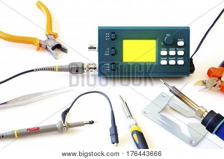 Modern digital signal oscilloscope and tools isolated on white background closeup