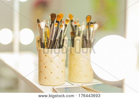 Brushes for make up standing near the mirror. Beautiful light and bokeh