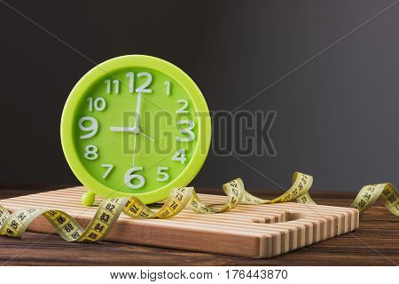 Close Up Of Green Clock And Measuring Tape