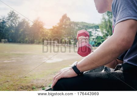 Handsome man doing push up exercise with dumbell