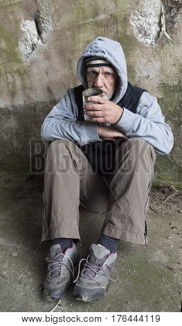 Mature homeless man begging with an empty tin