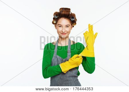 Young white red haired woman wears yellow rubber gloves with wavers on hair