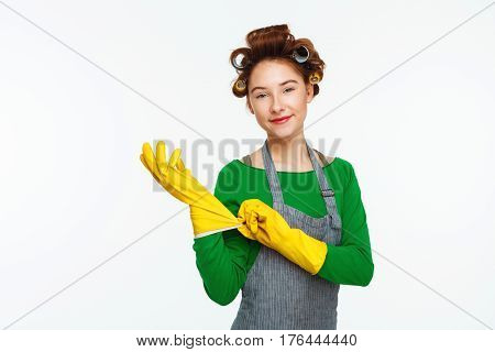 Nice young white woman puts on yellow rubber gloves on hands with curlers on hair smiling