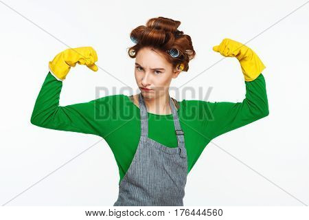 Pretty young housewife with curlers on hair shows power posing and making fun at camera