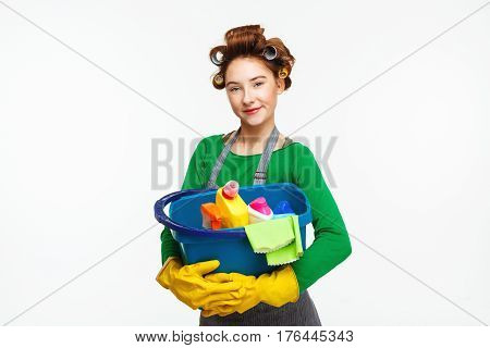 Adorable young housewife smiles and poses holding cleaning tools wearing yellow rubber gloves and curlers