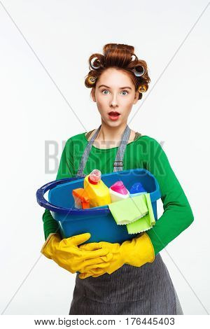 Surprised nice young woman in green uniform holds blue bucket full of different cleaning tools