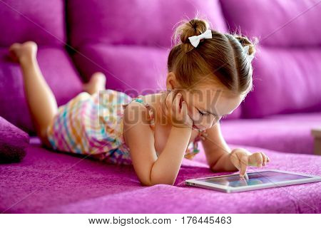 Little pretty girl with a tablet computer on a sofa at home