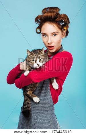 Nice beautiful girl with pretty cat in hands makes fun posing and looking to camera