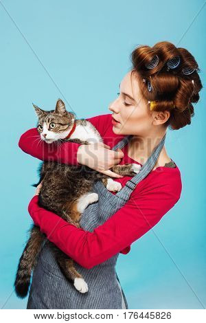 Woman with cat in hands play pose together for picture while cleaning house on blue