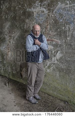 Mature homeless man standing in the cold