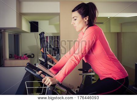 Fitness Woman Using Cycling Exercise Bike At Gym