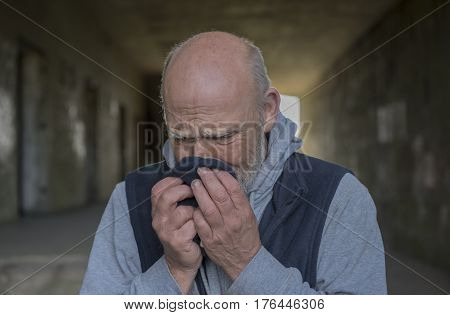 Mature homeless man crying into a rag