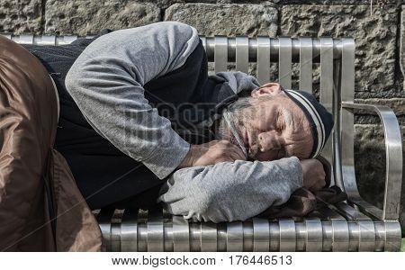 Mature homeless man sleeping on a bench
