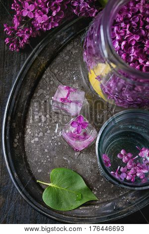 Glass and pitcher of lilac lemonade water with lemon, ice cubes with lilac flowers and lilac branch on vintage iron tray over black wooden table. Dark rustic style. Top view
