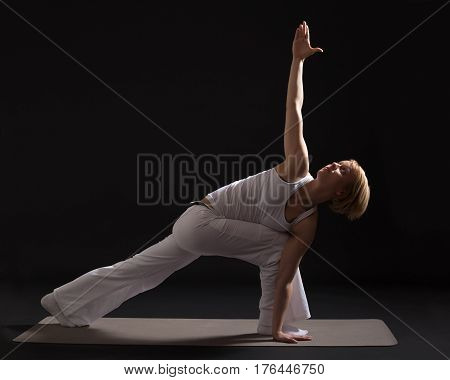 Woman exercising yoga indoor on black background,Bikram triangle   /Trikonasana