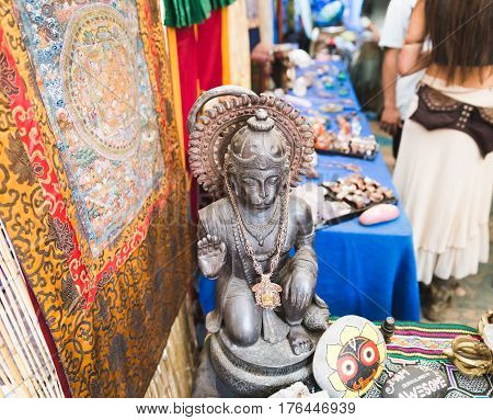 Religious sculpture jewelry tapestries and other decorations inside a booth at an outdoor event.