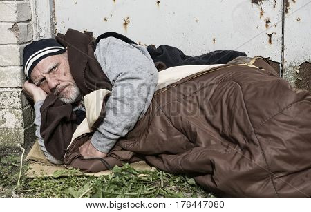 Mature homeless man sleeping rough on the streets