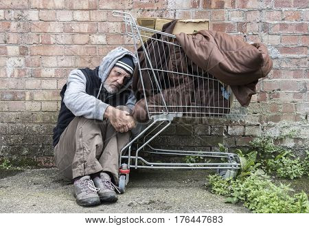 Mature homeless man leaning against a trolley full of his belongings