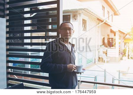 Asian man holding cup of coffee at home he look out of forward. Selective focus and soft flare filter.