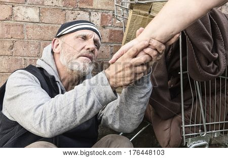 Mature homeless man taking an unrecognisable woman's hand