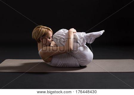 Woman exercising yoga indoor on black background,Wind Relieving pose/Pawanmuktasana