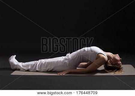 Woman exercising yoga indoor on black background,Fish pose/Matsyasana