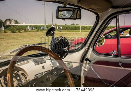 Interior of a Fiat 500 fully restored in view of a typical Italian countryside. Not just a car but an icon that created automotive history poster