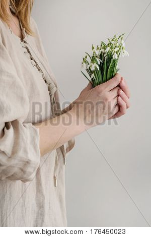 Bouquet of wild snowdrops in famale hands. Woman in white linen dress. Day light. Spring gift.