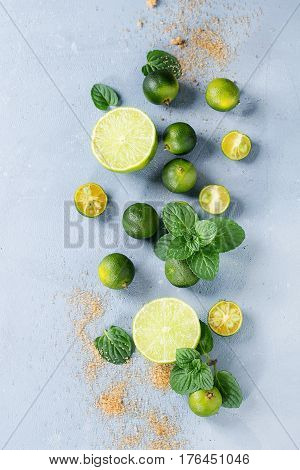 Ingredients for mojito cocktail, whole, sliced lime and mini limes, mint leaves, brown crystal sugar over gray stone texture background. Top view, space